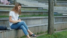 Young beautiful girl in a park writes to a notebook. A student writes poetry, keeps a diary. Sits on concrete. Young beautiful girl in a park writes to a stock footage