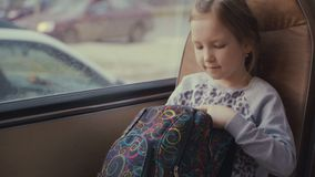 Young, beautiful girl passenger with school bag in the moving school bus using social network on her smartphone and
