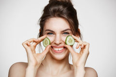 Young beautiful girl with perfect clean skin smiling looking at camera holding cucumber slices over white background. Beauty cosmetology and spa. Copy space Stock Image