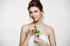 Young beautiful girl with perfect clean skin smiling looking at camera holding glass of water with cucumber slices over. White background. Healthy nutrition Stock Photo