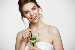Young beautiful girl with perfect clean skin smiling looking at camera holding glass of water with cucumber slices over. White background. Healthy nutrition Royalty Free Stock Images