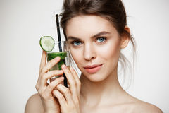 Young beautiful girl with perfect clean skin smiling looking at camera holding glass of water with cucumber slices over. White background. Healthy nutrition Royalty Free Stock Photography