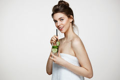 Young beautiful girl with perfect clean skin smiling looking at camera holding glass of water with cucumber slices over. White background. Healthy nutrition Royalty Free Stock Photos