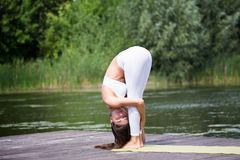 Young girl practices yoga on the shore of the lake, the concept of enjoying privacy and concentration, sunlight. Young, beautiful girl performs yoga asanas on stock photo