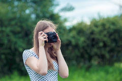 Young beautiful girl photographed in the old vintage camera. Young beautiful woman taking a photo by old fashioned vintage camera Stock Photography