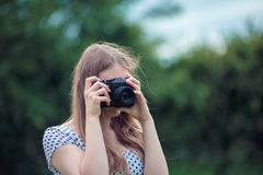 Young beautiful girl photographed in the old vintage camera. Young beautiful woman taking a photo by old fashioned vintage camera Stock Images