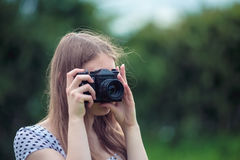 Woman taking picture with vintage camera. Young woman in countryside taking picture with vintage camera Royalty Free Stock Photography