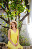 Young beautiful girl picking fresh ripe limes or lemons in sunny garden in Italy Stock Photography