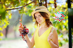 Young beautiful girl picking mellow grape in sunny day in Italy Stock Photo
