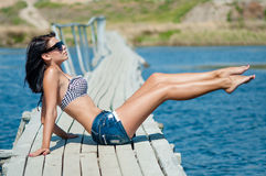 Young beautiful girl on the pier at the river in denim shorts Stock Image