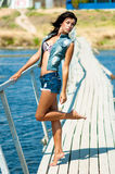 Young beautiful girl on the pier at the river in denim shorts Stock Photos