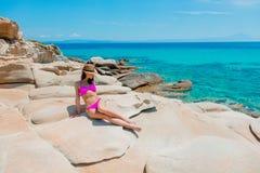 Young beautiful girl in pink bikini on a rock. Near a sea coast in Greece stock images