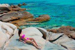 Young beautiful girl in pink bikini on a rock. Near a sea coast in Greece royalty free stock image