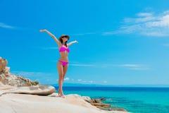 Young beautiful girl in pink bikini on a rock. Near a sea coast in Greece royalty free stock photos