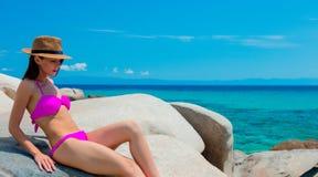 Young beautiful girl in pink bikini on a rock. Near a sea coast in Greece royalty free stock photo
