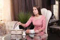 The girl in the cafe. Young beautiful girl in pink dress sits in a cafe and drinks coffee stock image