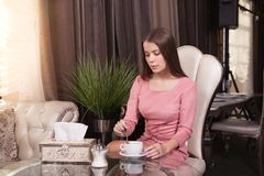The girl in the cafe. Young beautiful girl in pink dress sits in a cafe and drinks coffee stock photo
