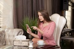 The girl in the cafe. Young beautiful girl in pink dress sits in a cafe uses the phone and drinks coffee stock photo