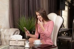 The girl in the cafe. Young beautiful girl in pink dress sits in a cafe uses the phone and drinks coffee royalty free stock photography
