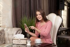 The girl in the cafe. Young beautiful girl in pink dress sits in a cafe uses the phone and drinks coffee stock images