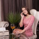 The girl in the cafe. Young beautiful girl in pink dress sits in a cafe uses the phone and drinks wine royalty free stock photos