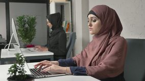 Young beautiful girl in pink hijab and glasses typing, working on computer. Look at the camera, smiling. Arab women in. The office. Girl in black hijab in stock video footage