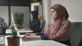 Young beautiful girl in pink hijab and glasses typing, working on computer. Look at the camera, smiling. Arab women in. The office. Girl in black hijab in stock video