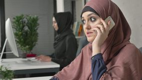 Young beautiful girl in pink hijab sits in the office and speaks on the smartphone, laughing. 60 fps