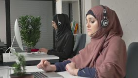 A young beautiful girl in a pink hijab is talking on the headset, answering calls in call center. Arab women in the stock footage