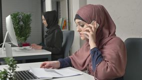 Young beautiful girl in pink hijab working with documents and talking on mobile phone. Arab women in the office. 60 fps stock video