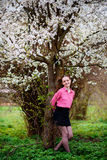 Young beautiful girl in a pink shirt standing under blossoming apple tree and enjoying a sunny day. Stock Photos