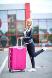 A girl with a pink suitcase stands on the street close up Royalty Free Stock Photography