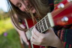 Young beautiful girl playing on acoustic guitar. Stock Image