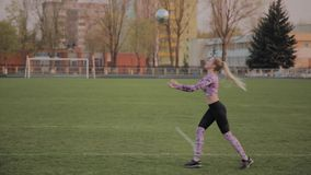 Young beautiful girl playing with a ball at the stadium. Young beautiful girl playing with a ball at the stadium stock video footage