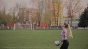 Young beautiful girl playing with a ball at the stadium. Young beautiful girl playing with a ball at the stadium stock footage