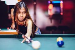 Young beautiful girl playing billiard in a club Stock Photo