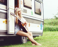 Young and beautiful girl playing guitar outdoors. Holiday, journ Stock Photography