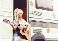 Young and beautiful girl playing guitar outdoors. Holiday, journ Royalty Free Stock Photo