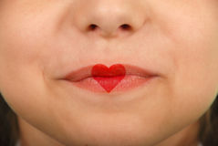 Young beautiful girl playing with heart drawing on lips. Valentines day beautiful love make-up stock images