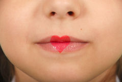 Young beautiful girl playing with heart drawing on lips. Valentines day beautiful love make-up stock photos
