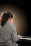 Young beautiful girl playing the piano Stock Images