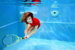 Young beautiful girl playing tennis underwater in the swimming pool Royalty Free Stock Photography