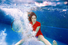 Young beautiful girl playing tennis underwater in the swimming pool Royalty Free Stock Photo