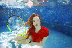 Young beautiful girl playing tennis underwater in the swimming pool Stock Photos