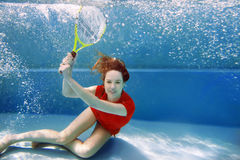 Young beautiful girl playing tennis underwater in the swimming pool Stock Photography