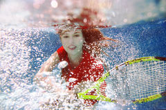 Young beautiful girl playing tennis underwater in the swimming pool Royalty Free Stock Images