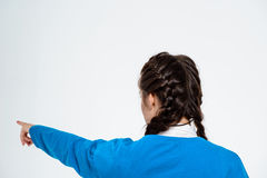 Young beautiful girl pointing finger away over white background. stock photos
