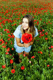 Young beautiful girl in a poppies field Royalty Free Stock Photo