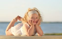 Young beautiful girl posing for the camera in white dress Royalty Free Stock Images