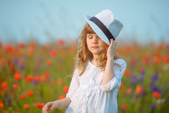 Young beautiful girl posing in a hat near the blooming poppy fie Royalty Free Stock Photography